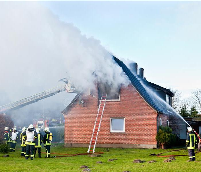 Firefighters putting out a fire in a house