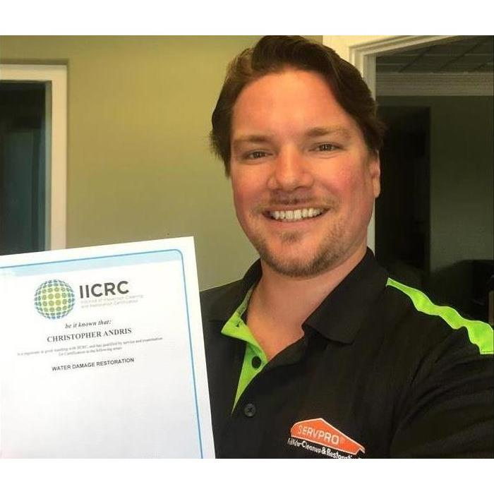 General manager holding a certificate for water damage restoration