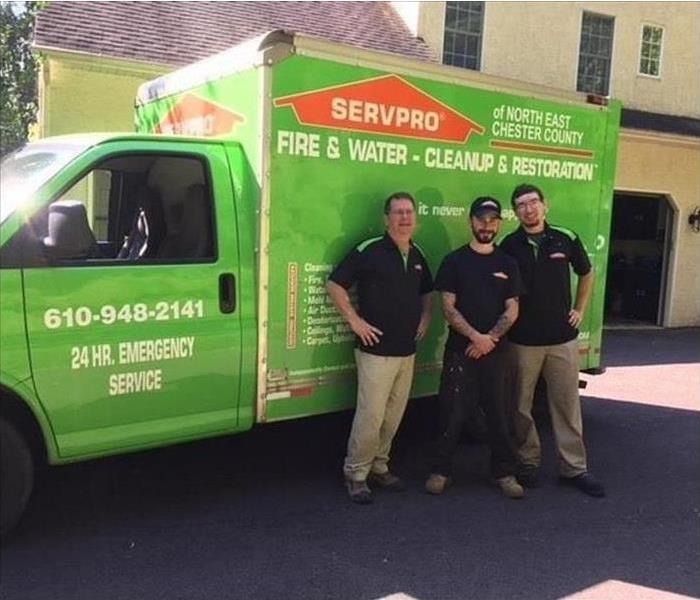 Three employees in front of a SERVPRO box truck getting their picture taken